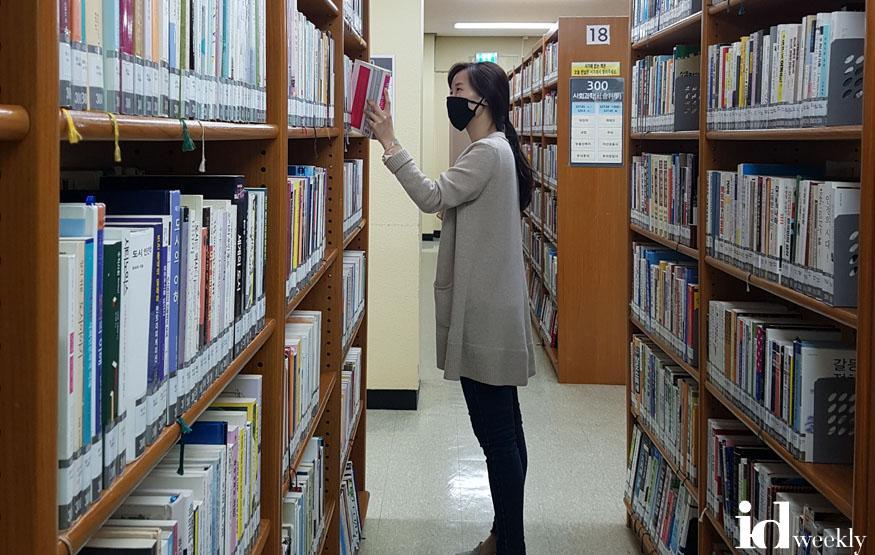 도서관지원과-부분 개관하는 성남시 공공도서관 자료실에서 대출할 책을 고르고 있다.jpg