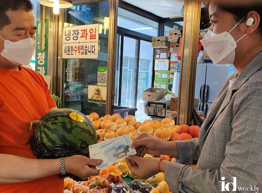 여성가족과-캄보디아 출신 결혼이민자가 성남 중앙시장에서 성남사랑상품권으로 수박을 사고 있다.jpg